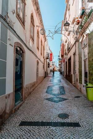 Schmale Gasse Rua Silva Lopes in Lagos, Portugal mit alten Pflastersteinen mit eingearbeitetem Muster