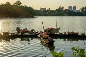 Schmale Holzboote mit Blumen auf See in Ho Chi Minh City mit Sonnenuntergang über Hochhäusern