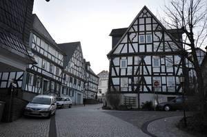 Schmale mit Basaltsteinen gepflasterte Straße mit geparkten Autos zwischen weißen Fachwerkhäusern