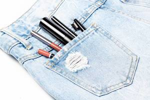 Schminksachen für Frau in einer Jeanshosentasche, Nahaufnahme vor weißem Hintergrund