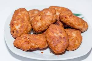 Schnitzel aus goldgelb gebratenem Fleisch auf weißem Teller
