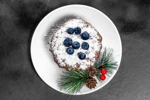 Schoko-Cupcake mit Puderzucker und frischen Heidelbeeren auf einem Teller mit Weihnachtsdeko, Aufnahme von oben vor schwarzem Hintergrund