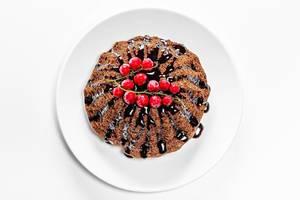 Schoko-Cupcake mit roten Waldfrüchten und Schoko-Topping: Aufnahme von oben auf weißem Hintergrund