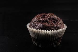 Schokoladen-Muffinplätzchen auf dem schwarzen Hintergrund