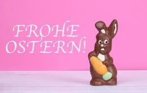Schokoladen-Osterhase auf einem Holztisch vor Text Frohe Ostern auf rosa Hintergrund