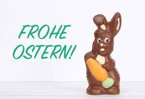 Schokoladen-Osterhase auf einem Holztisch vor Text Frohe Ostern auf weißem Hintergrund