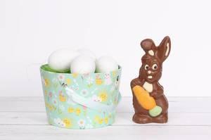 Schokoladen-Osterhase neben einem Eimer mit grünem Gras und weißen Ostereiern auf einem Holztisch mit weißem Hintergrund