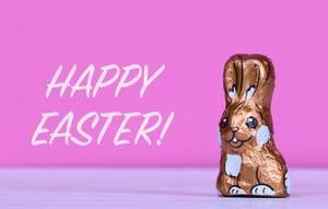 Schokoladen-Osterhase neben Text Happy Easter mit rosa Hintergrund