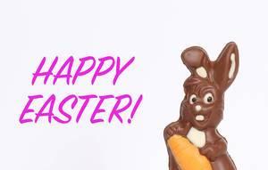 Schokoladen-Osterhase neben Text Happy Easter vor weißem Hintergrund