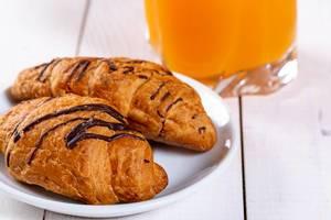 Schokoladencroissants auf einem Teller mit Orangensaft im Hintergrund