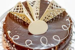Schokoladenkuchen mit weißer Dekoration für Grußbotschaft zu Geburtstag oder Jubiläum