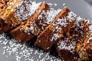 Schokoladenkuchen-Rolle, geschnitten, mit Kokosraspeln bestreut