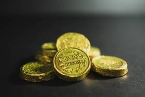 """Schokoladenmünzen in goldener Verpackung mit dem spanischen Aufdruck """"Dos Pesos"""", auf schwarzem Untergrund"""
