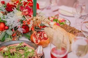 Schön dekorierter Tisch mit Roastbeef und Brot, Gläsern, Blumengesteck und grüner Kerze