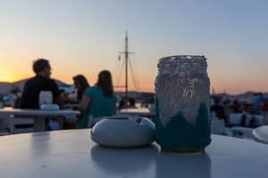 Schön verziertes Kerzenglas neben Aschenbescher vor Sonnenuntergang am Hafen von Paros