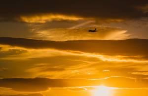 Schöne Sonnenuntergangsszene mit Reise-Flugzeug, klar zu erkennen am orangen Himmel