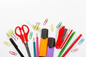 School supplies on white background. Markers, scissors, pencils and paper clips