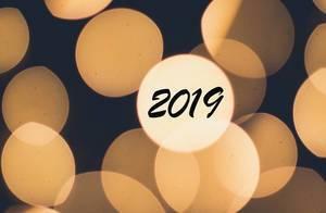 Schriftzug 2019 in hellen Bokeh Lichtern, gelben Lichterkreisen vor dunklem Hintergrund