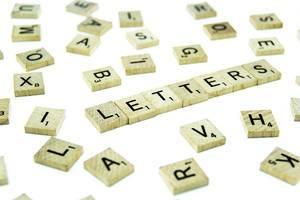 Schriftzug LETTERS auf Holzplättchen zwischen unsortierten Scrabble-Steinen