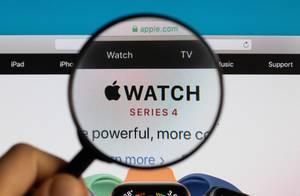 """Schriftzug mit integriertem Logo der Smartwatch von """"Apple Watch - Series 4"""",  vergrößert durch eine Lupe dargestellt"""