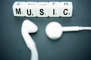 Schriftzug MUSIC dargestellt mit weißen Würfeln neben weißen In-Ear-Kopfhörern
