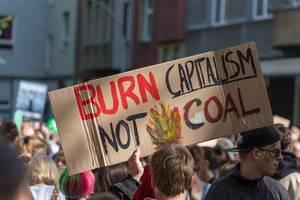 """Schriftzug """"Burn Capitalism! Not Coal"""" umgeben von zahlreichen Klimademonstranten"""