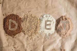 """Schriftzug """"Diet"""" (deutsch: Diät) im Getreide, bestehend aus natürlichem Buchweizen, Gerste und Reis, auf braune Backpapier"""