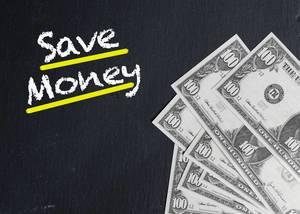 Schriftzug SAVE MONEY (Geld sparen) und Banknoten auf schwarzem Hintergrund