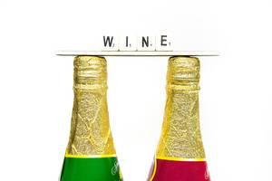 Schriftzug WINE über zwei Flaschen mit goldenem Deckel vor weißem Hintergrund