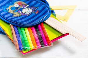 Schultasche mit bunten Stiften, Bastelpapier und Lineal vor weißem Hintergrund