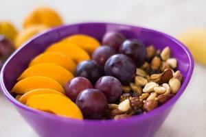 Schüssel Granola mit Trauben und Pfirsichscheiben