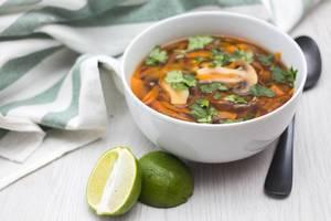 Schüssel mit asiatischer Suppe mit Pilzen, Karotten und Limette neben Löffel und Serviette