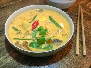 Schüssel mit Curry mit Pilzen, Bohnen und Petersilie neben Essstäbchen auf Holztisch