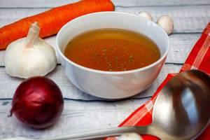 Schüssel mit Fleischbrühe und Gemüse drumherum