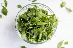 Schüssel mit Rucola Salat von oben fotografiert auf weißem Hintergrund
