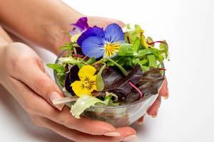 Schüssel mit Salatblätter, Arugula und Blumen in weiblicher Hand