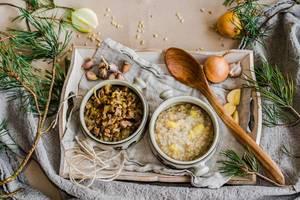Schüsseln mit Perlgerstenbrei, Fleisch und Gemüse auf Holztablett mit Knoblauch und Zwiebeln