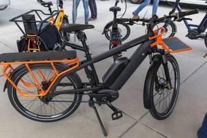Schwarz-oranges gepäckraumoptimiertes E-Bike von Riese & Müller, als Ausstellungsstück für nachhaltige umweltfreundliche Elektrofahrzeuge