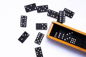 Schwarz-weiße Dominosteine liegen neben Holzkiste auf weißem Tisch