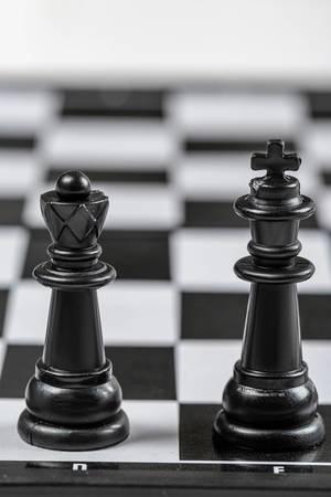 Schwarze Königin und König stehen auf einem Schachbrett
