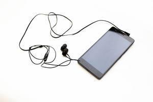 Schwarze Kopfhörer eingesteckt in Mobiltelefon mit ausgeschaltetem Bildschirm vor weißem Hintergrund