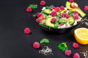 Schwarze Schale mit grünem Salat, Avocado-Scheiben, Himbeeren, Mikrogrün und anderen Zutaten auf schwarzem Hintergrund