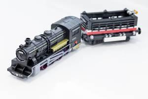 Schwarze Spielzeuglokomotive mit Anhänger, auf weißer Oberfläche