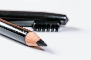 Schwarzer Augenbrauenstift und Brauenbürste vor weißem Hintergrund
