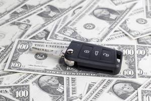 Schwarzer elektrischer Autoschlüssel liegt auf verteilten US-Dollar Banknoten