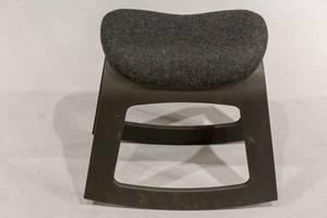 Schwarzer Hocker aus Kunststoff mit Sitzfläche bezogen mit Filz vor weißem Hintergrund
