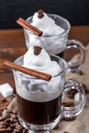 Schwarzer Kaffee mit Schlagsahne und Zimtstange im rustikalen Setting