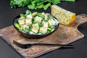 Schwarzer Teller mit frischem Salat, würzigen Käsewürfeln, Avocado-Scheiben und Petersilie auf einem Holzschneidebrett mit schwarzer Gabel und Stück Käse