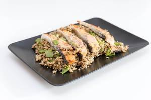 Schwarzer Teller mit schön angerichteten Lachssteifen mit Blumenkohl-Quinova und Parmesan