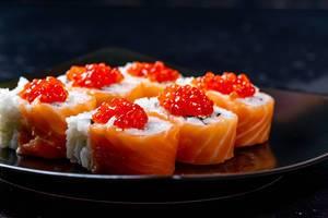 Schwarzer Teller mit sechs Philadelphia Sushi Rollen mit Lachs, Käse und Kaviar-Topping